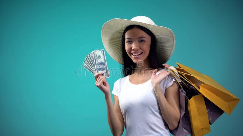 Asiatin im Sonnenhut, der gro?e Summe Dollar und viele Einkaufstaschen, Darlehen h?lt stockfoto