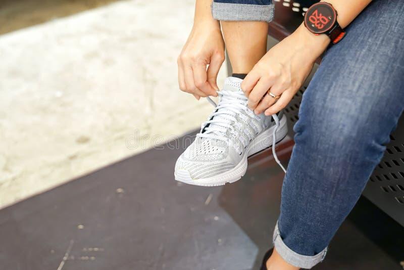 Asiatin ist, vorher, tragend und prüfend den Turnschuh im Schuhgeschäft, um es zu kaufen lizenzfreie stockbilder
