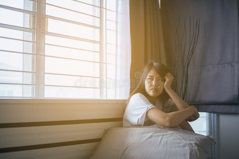 Asiatin lassen Kopfschmerzen auf Bett nach morgens aufwachen lizenzfreie stockbilder