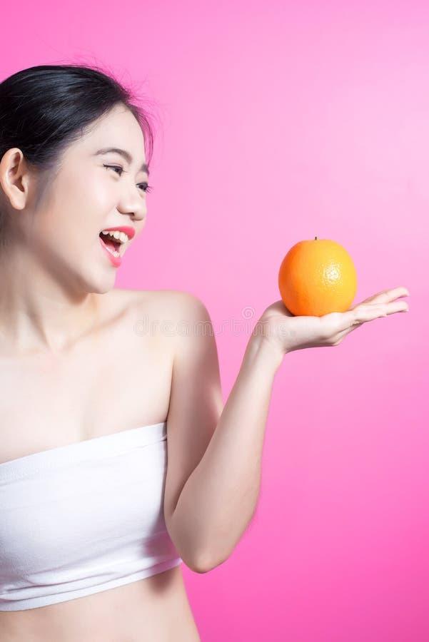 Asiatin mit orange Konzept Sie lächelnd und Orange halten Schönheitsgesicht und natürliches Make-up einfach für Sie ändern Sie Fa lizenzfreies stockbild