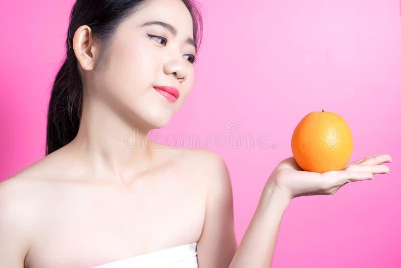Asiatin mit orange Konzept Sie lächelnd und Orange halten Schönheitsgesicht und natürliches Make-up einfach für Sie ändern Sie Fa stockfotografie