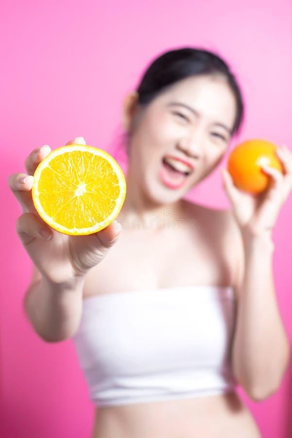 Asiatin mit orange Konzept Sie lächelnd und Orange halten Schönheitsgesicht und natürliches Make-up einfach für Sie ändern Sie Fa lizenzfreies stockfoto