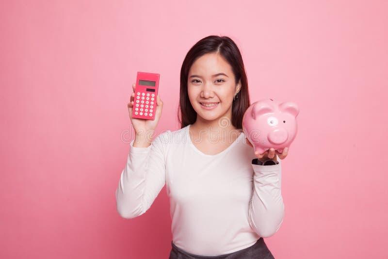 Asiatin mit Taschenrechner und Sparschwein lizenzfreie stockbilder