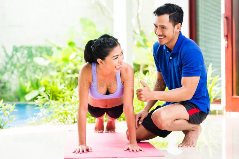 Asiatin und persönlicher Trainer an der Sportübung stockbild