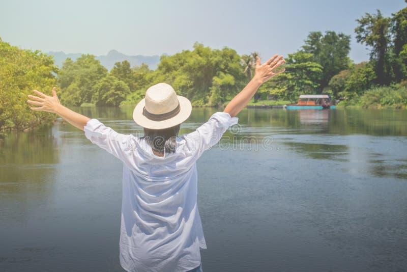 Asiatinabnutzungs-Webarthut und weißes Hemd mit Stellung auf hölzerner Terrasse, lizenzfreies stockfoto