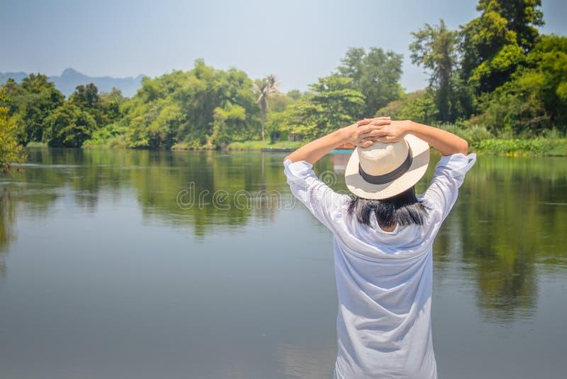 Asiatinabnutzungshut und weißes Hemd mit Stellung auf Holzbrücke, sie vorwärts schauend zum Fluss mit ihrs Hand auf Kopf und s ge stockbilder