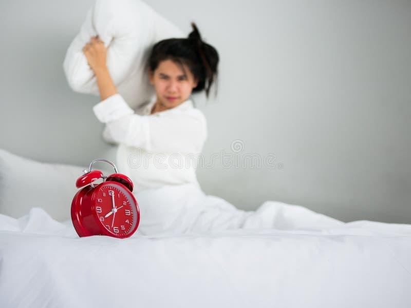 Asiatinfrau, die ein Kissen am Wecker im mornin wirft lizenzfreie stockfotografie