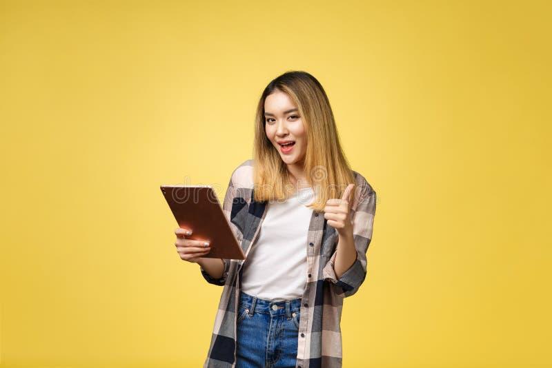 Asiatingebrauch des Tabletten-PC und -daumens herauf Isolat auf yello Hintergrund stockbilder