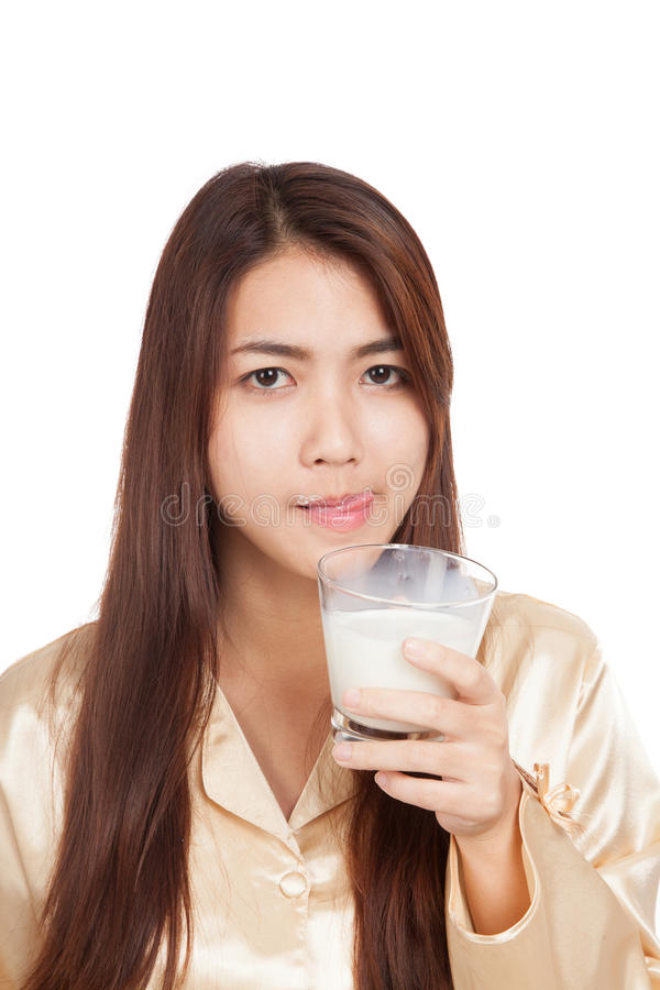 Asiatingetränkmilch, die ihre Lippe leckt lizenzfreie stockbilder