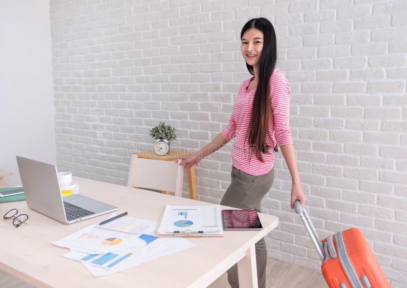 Asiatinholding-Reisekoffer, der von der Arbeit auf Tabelle und zu den Feiertagsferien sich vorbereiten verlässt Aus Bürokonzept h stockfotos