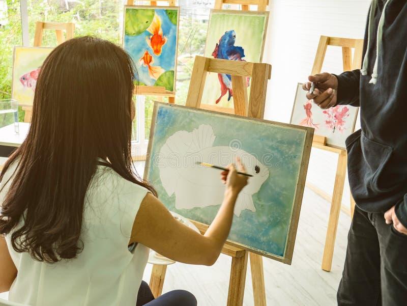 Asiatinnen artrist, das die Fische im Klassenzimmer während ihr Lehrerunterricht und unterrichten, wie man malt malt lizenzfreie stockbilder