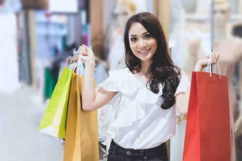Asiatinnen und schönes Mädchen hält das Einkaufstaschelächeln stockbilder