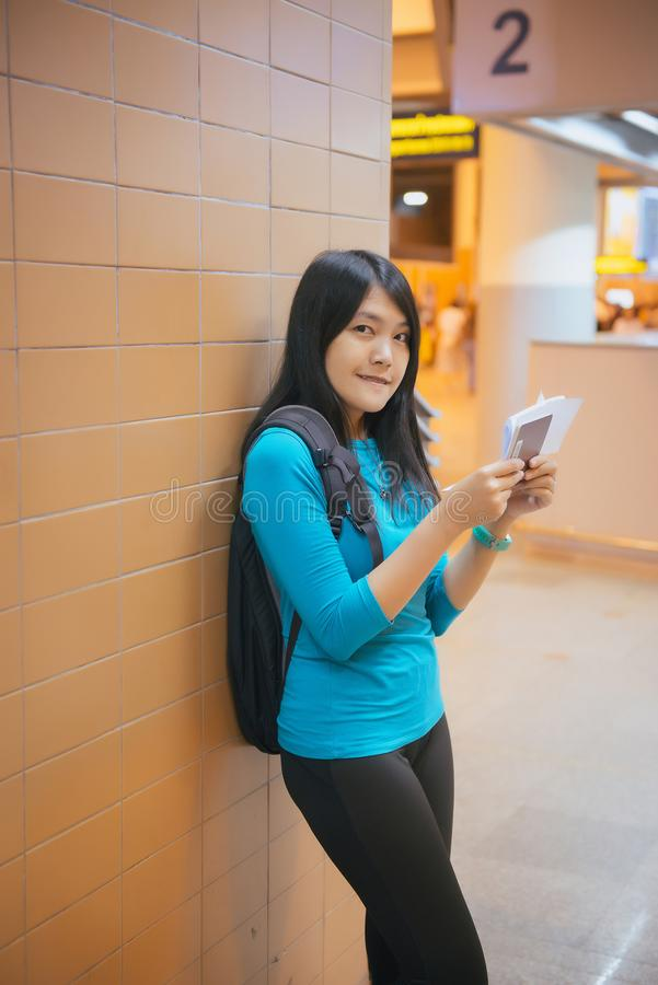 Asiatinpassagier, der Smartphone und Prüfungsflug oder on-line-Abfertigungs- halten und Reiseplaner am internationalen Flughafen stockfotos