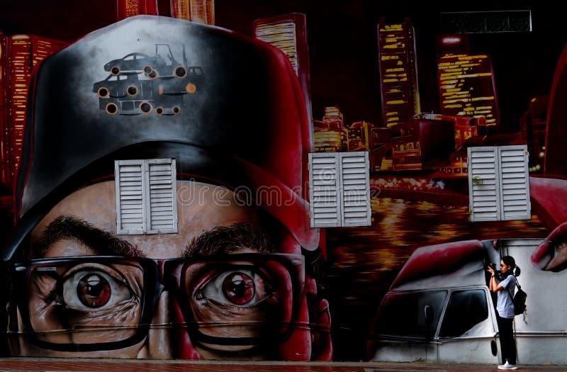 Asiatintourist, der Fotostraßen-Kunstgraffiti an Singapur-Markstein nahe Singapur-Fluss nimmt Betonmauer des Geb?udes stockbilder