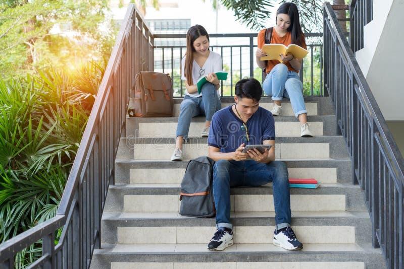 Asiatique d'université d'étudiants lisant ensemble l'étude de livre photos stock