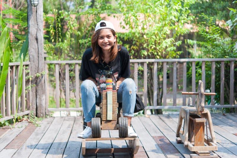 Asiatique de jeune femme elle monte un cheval en bois de jouet sur l'esprit de carrousel photo libre de droits