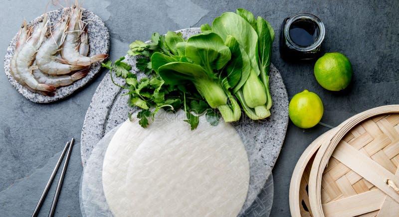 Asiatique faisant cuire des ingrédients : papper de riz, pok choy, sauces, crevettes crues Cuisine chinoise ou thaïlandaise de co photo libre de droits