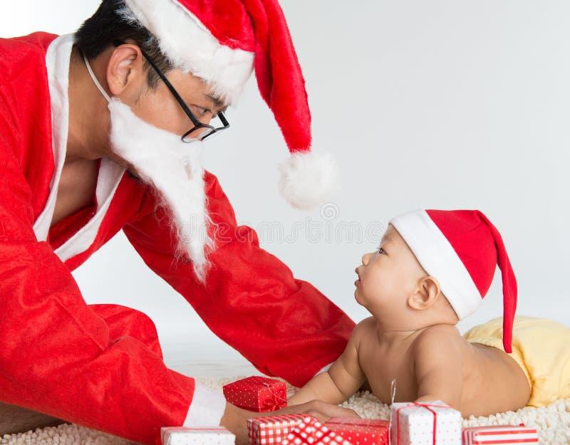 Asiatique le père noël avec le bébé images stock