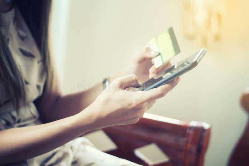 Asiatique mol de femme de foyer employant le téléphone et les achats futés de carte de crédit photos stock