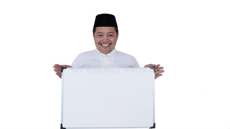 Asiatique musulman avec la position de poids excessif et tenir le conseil blanc présent l'espace coppy photographie stock libre de droits