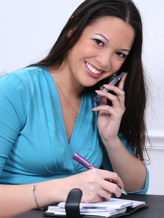 Asiatisch-Amerikanische Frau mit Mobiltelefon und Datebook stockfotografie