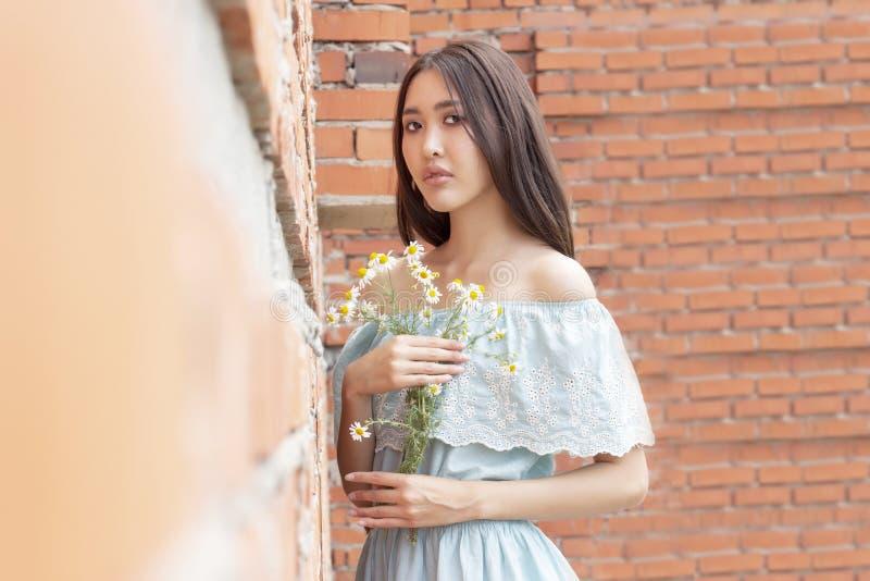 Asiatisch-aussehendes Mädchen mit einem Blumenstrauß der Kamille in ihren Händen, die gegen Wand des roten Backsteins stehen stockfotos