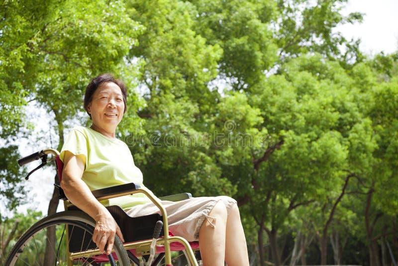 Asiatische ältere Frau, die auf einem Rollstuhl sitzt lizenzfreies stockfoto