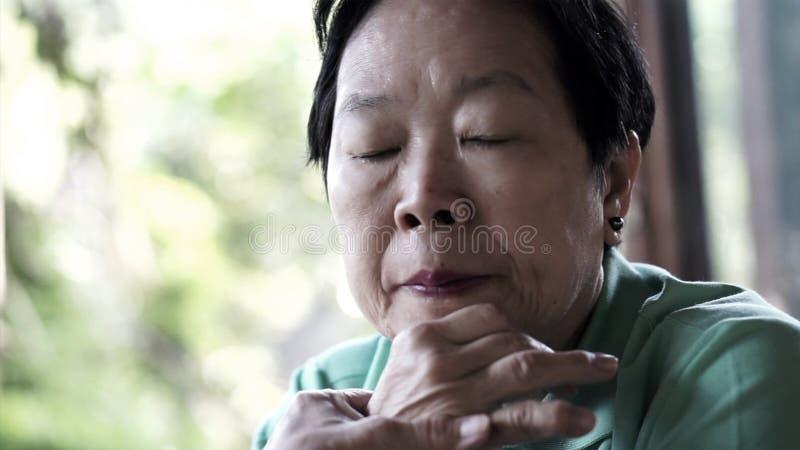 Asiatische ältere Frau mit der Hand auf Gesicht denkend, Sorge traurig stockfotografie