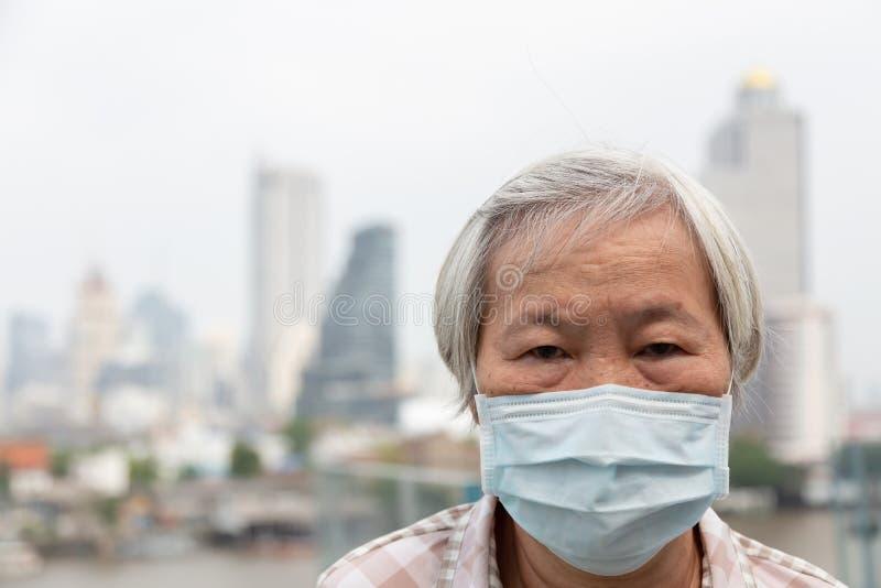 Asiatische ?ltere Frau mit Gesichtsmaskeschutz, tragende Gesichtsmaske der ?lteren Frau wegen der Luftverschmutzung im Stadtgeb?u lizenzfreies stockbild