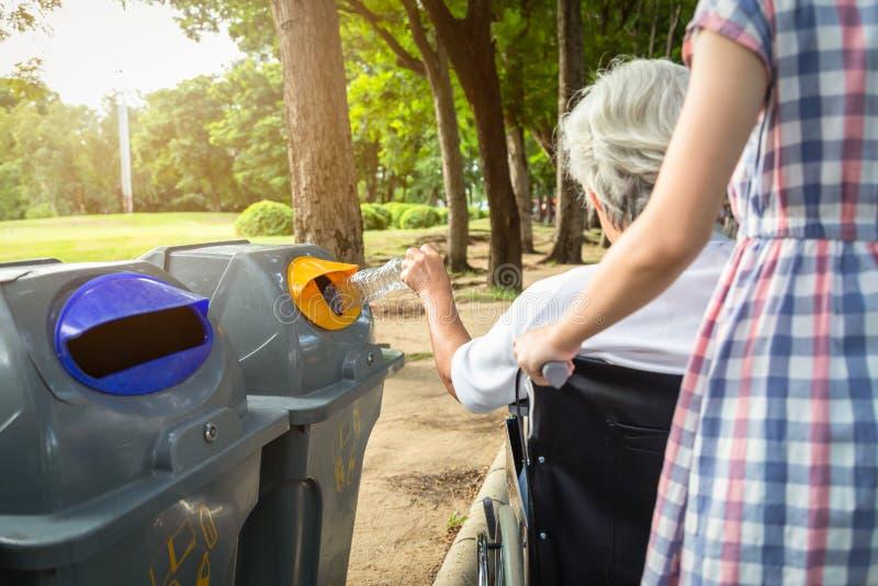 Asiatische ältere Frauenhand, welche die Plastikflasche, Plastikwasserflasche in Wiederverwertungsbehälter einsetzend, ältere tou stockbild