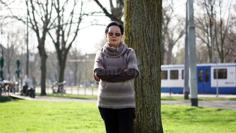 Asiatische ältere Frauenreise in Europa, das Porträt im Park nimmt lizenzfreie stockfotos