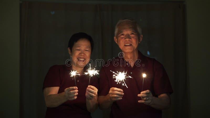 Asiatische ältere Paare, die Wunderkerzen, Feuercracker nachts spielen Konzept, welches das Leben feiert stockfotografie