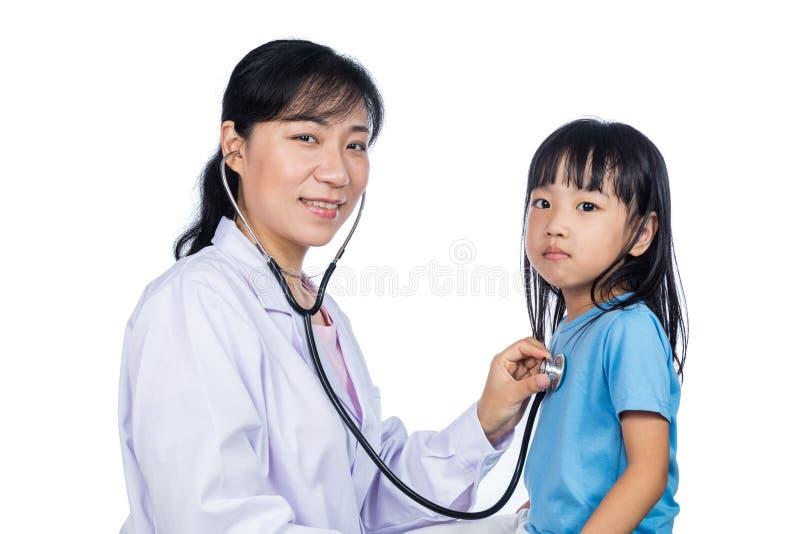 Asiatische Ärztin, die ein chinesisches kleines Mädchen durch stethosco überprüft stockfotografie
