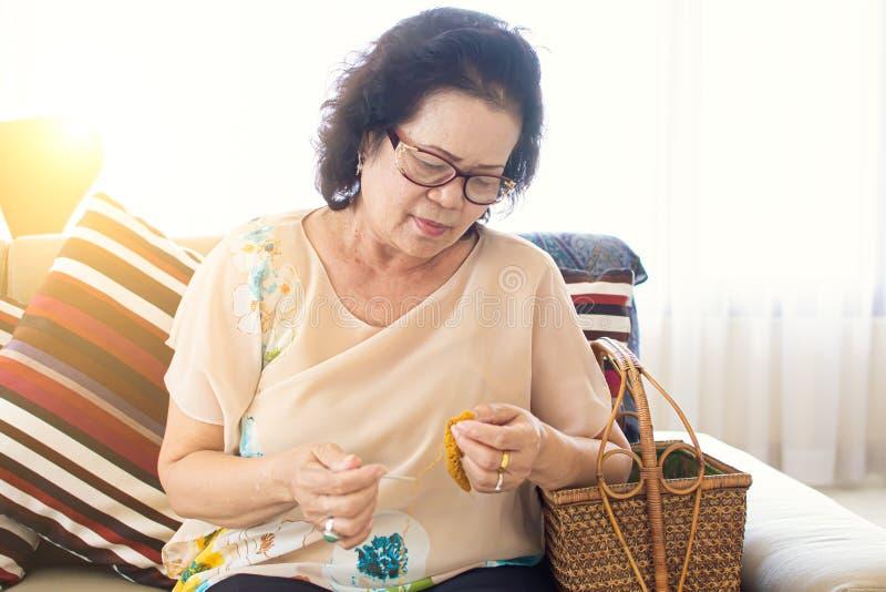 Asiatische alte Frau strickt Häkelarbeit im Raum stockbild