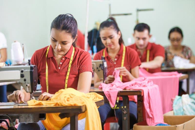 Asiatische Arbeitskräfte in der Kleiderfabrik nähend mit industriellem nähendem m lizenzfreies stockbild