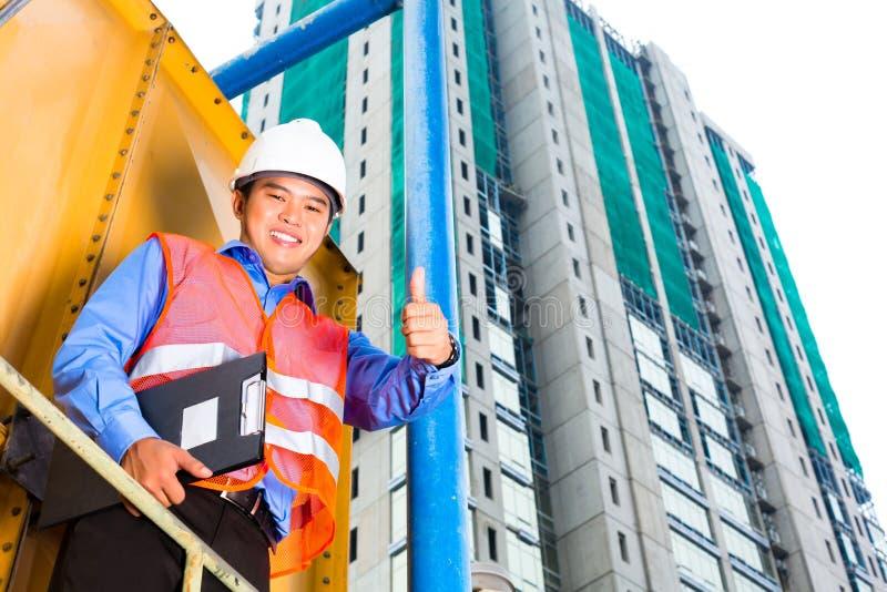 Asiatische Arbeitskraft oder Aufsichtskraft auf Baustelle stockfotos
