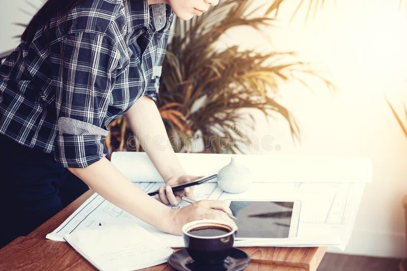 Asiatische Architektenfrau, die zu Hause mit Tablette und Plänen arbeitet stockbilder