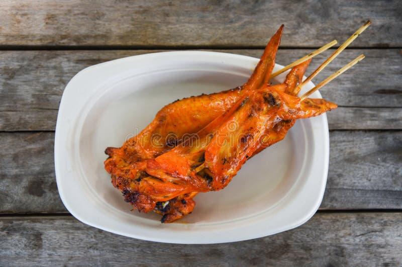 Asiatische Art gegrillter Hühnerflügel auf hölzernem Hintergrund des Behälters/thailändischen Brathühneraufsteckspindelnstöcken lizenzfreies stockfoto