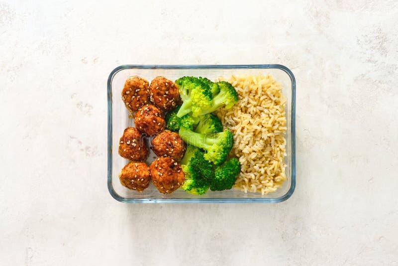 Asiatische Arthühnerfleischbälle mit Brokkoli und Reis in einem Nehmen stockbilder