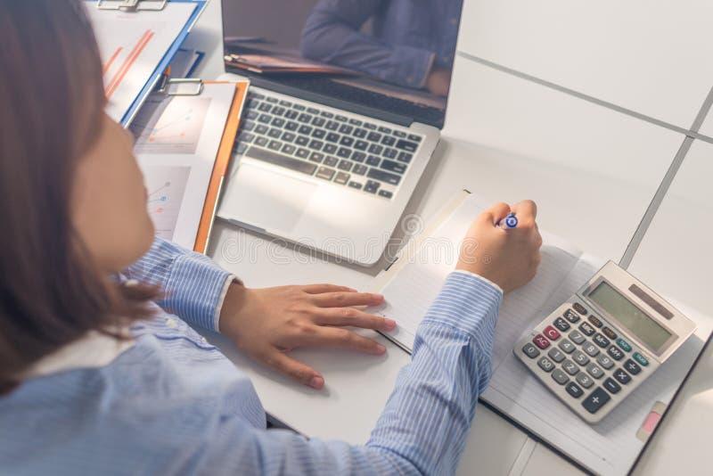 Asiatische Bürofrau, die Anmerkung in den Geschäftsraum schreibt lizenzfreie stockbilder