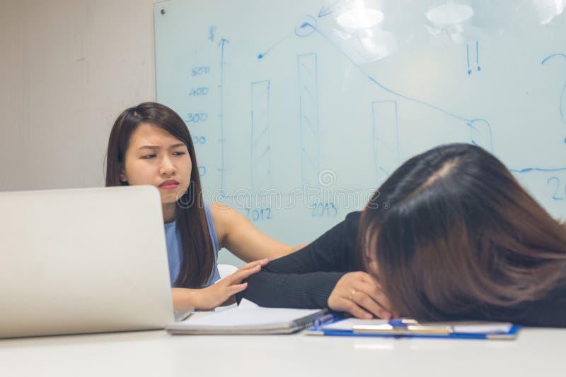 Asiatische Bürofrauensorge über müden Workmate lizenzfreies stockbild