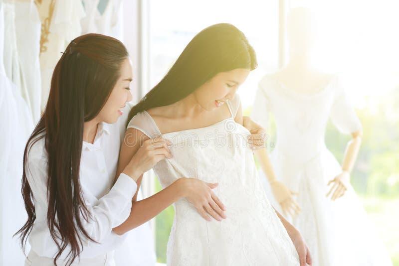 Asiatische Blickfrau, die auf Hochzeitskleid versucht und durch stylis unterstützt stockfotografie