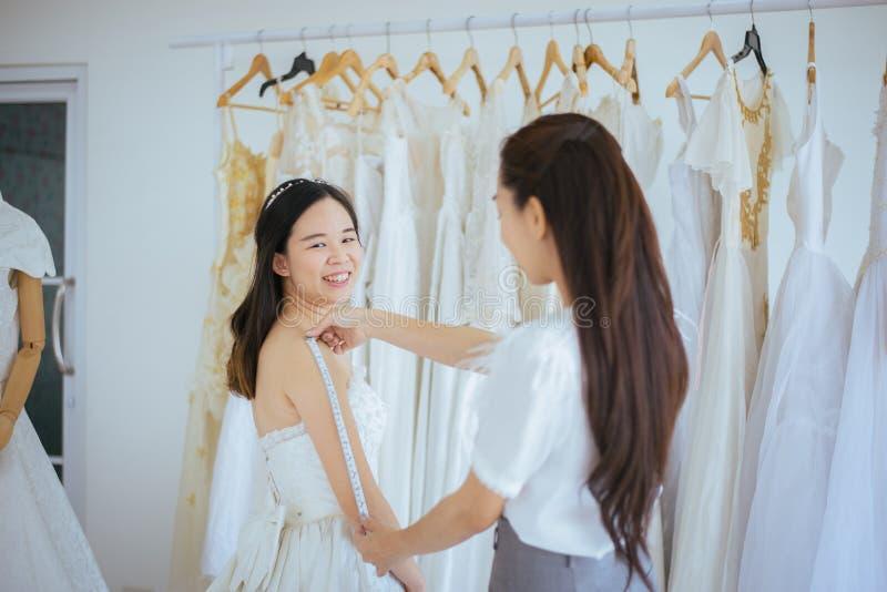 Asiatische Braut, die auf Hochzeitskleid, dem Frauendesigner in Mode machen Studio der Anpassung, glücklichem und das Lächeln ver stockfoto