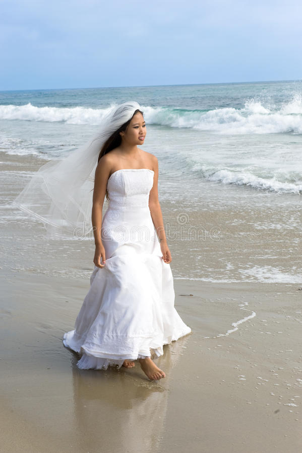Asiatische Braut im Hochzeitskleid am Strand lizenzfreie stockfotografie