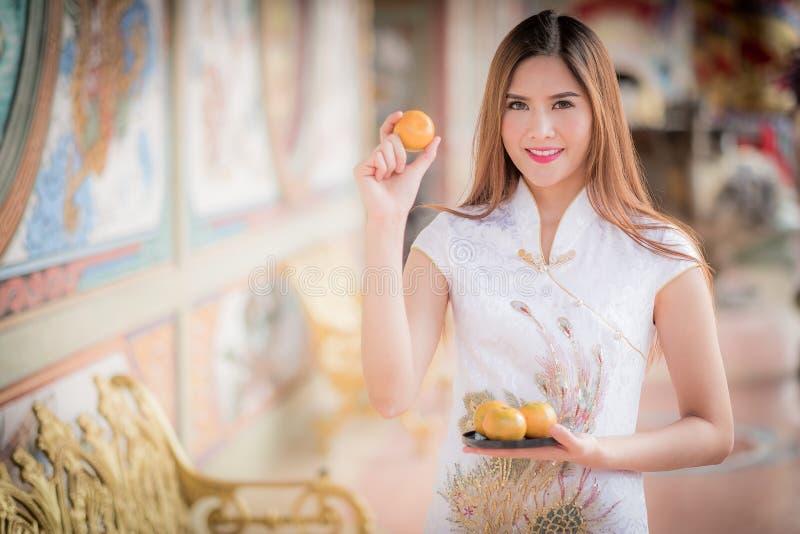 Asiatische Chinesin auf den traditionellen Chinesen, der orange Lohn bezüglich hält lizenzfreies stockfoto