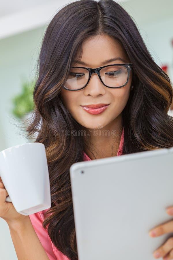 Asiatische Chinesin, die Tablet-Computer-trinkenden Kaffee oder Tee verwendet stockfoto