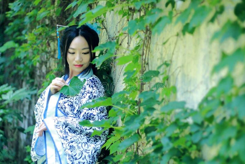 Asiatische Chinesin in traditionellem blauem und weißem Hanfu-Kleid, Spiel in einem berühmten Garten nahe Wand stockfoto