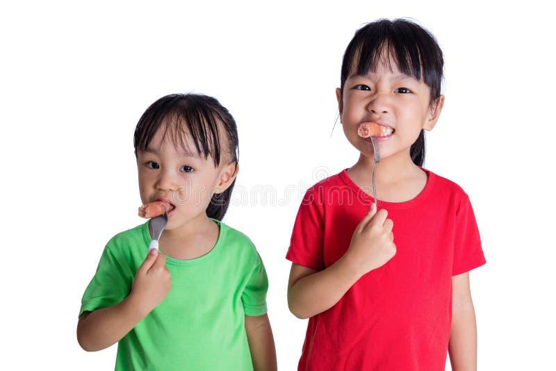 Asiatische chinesische kleine Mädchen, die Wurst essen lizenzfreie stockbilder