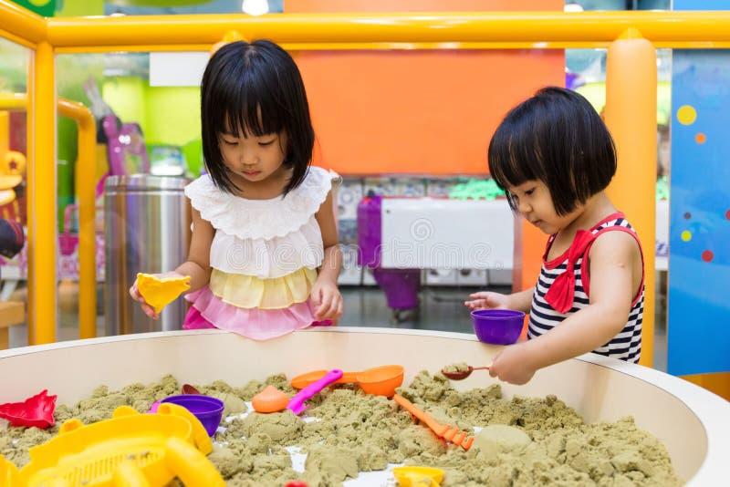 Asiatische chinesische kleine Schwester Playing Kinetic Sand Innen stockbild