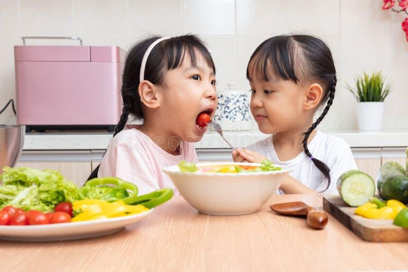 Asiatische chinesische kleine Schwestern, die zu Hause Salat in der Küche machen stockfotografie